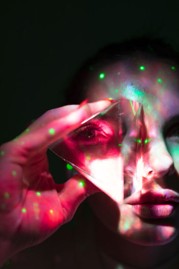 Close-up portrait of woman holding illuminated lighting equipment