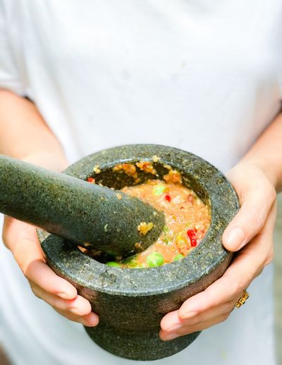 Namprik - Thai chili shrimp paste in stone mortar Holding One Person Food And Drink Food Human Hand Midsection Preparation  Real People Healthy Eating Lifestyles Human Body Part Freshness Indoors  Close-up Day Ready-to-eat People Stone Mortar Shrimp Paste Chili  Thai Food Healthy Food Thailand Spicy Food