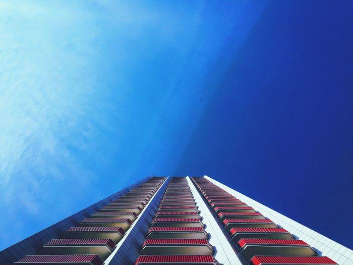 Directly below shot of modern building against blue sky