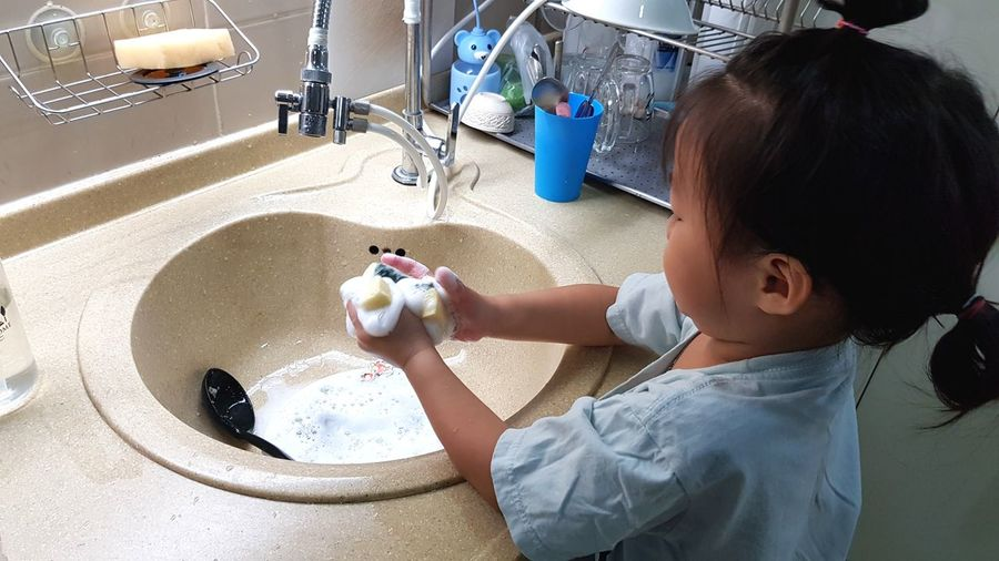High angle view of cute girl washing utensils at home