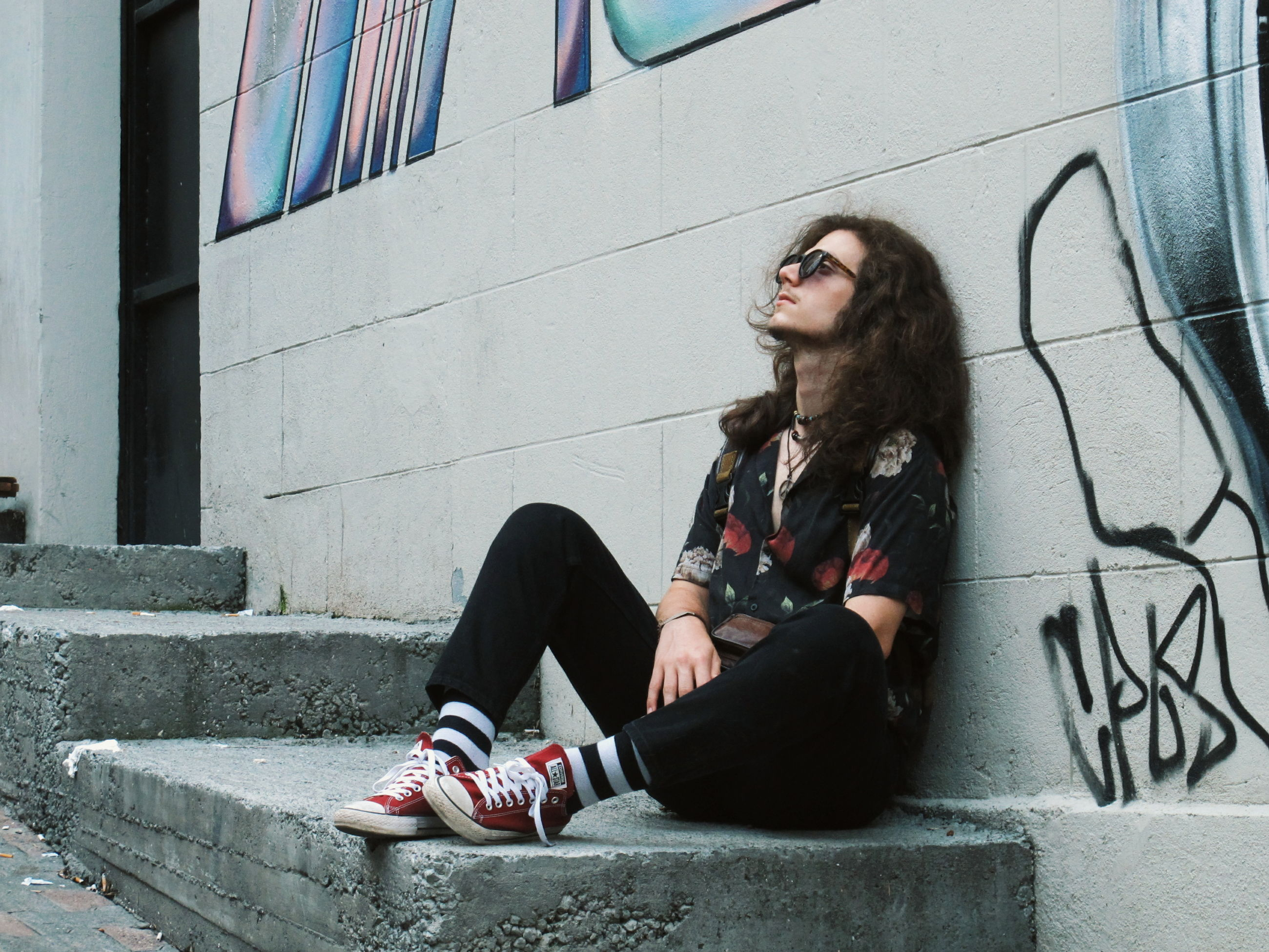 FULL LENGTH PORTRAIT OF YOUNG WOMAN SITTING AGAINST WALL