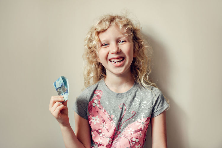 Portrait of laughing girl holding banknote standing against wall