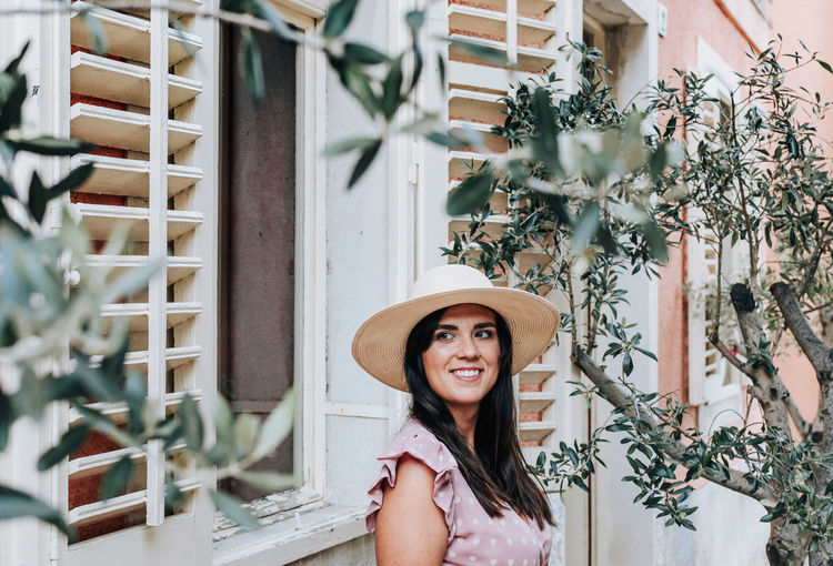 Beautiful young woman standing under olive tree, fashion, summer, happy, smiling, lifestyle.