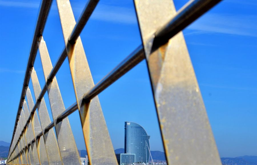 Power Lines fence Power Lines industrial landscapes eye4photography HotelW HotelW Power Lines Fence Power Lines Industrial Landscapes Eye4photography  Barcelona Architecture Sky Built Structure Fence Low Angle View Metal No People Blue Day Sunlight Chainlink Fence Building Exterior Clear Sky