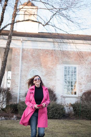 Portrait of woman in sunglasses walking against building