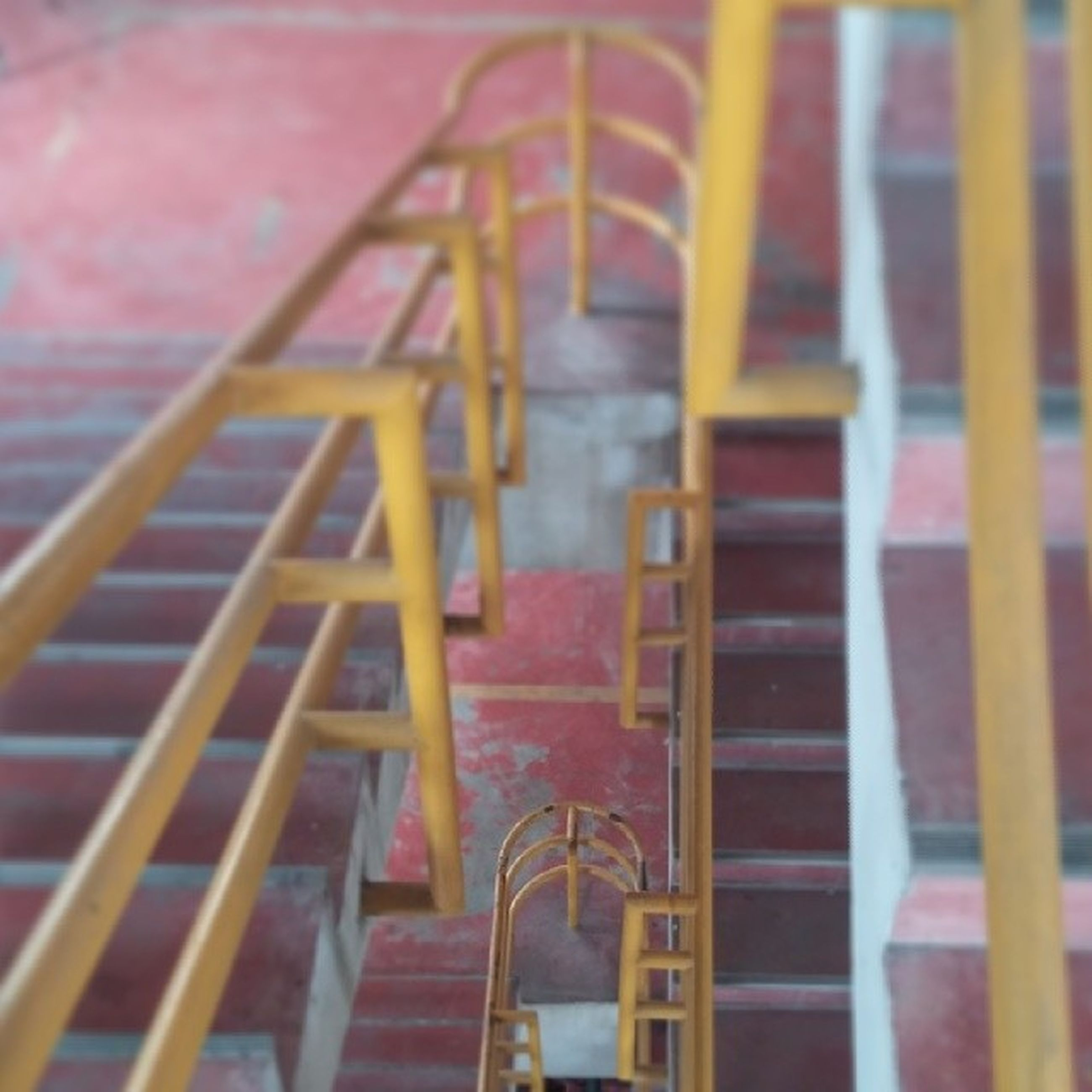 railing, steps, steps and staircases, staircase, metal, high angle view, built structure, lifestyles, red, outdoors, leisure activity, day, architecture, childhood, pattern, wood - material, sunlight