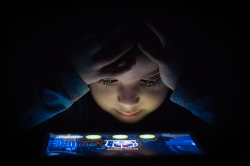 Portrait Of Young Boy Playing On Tablet