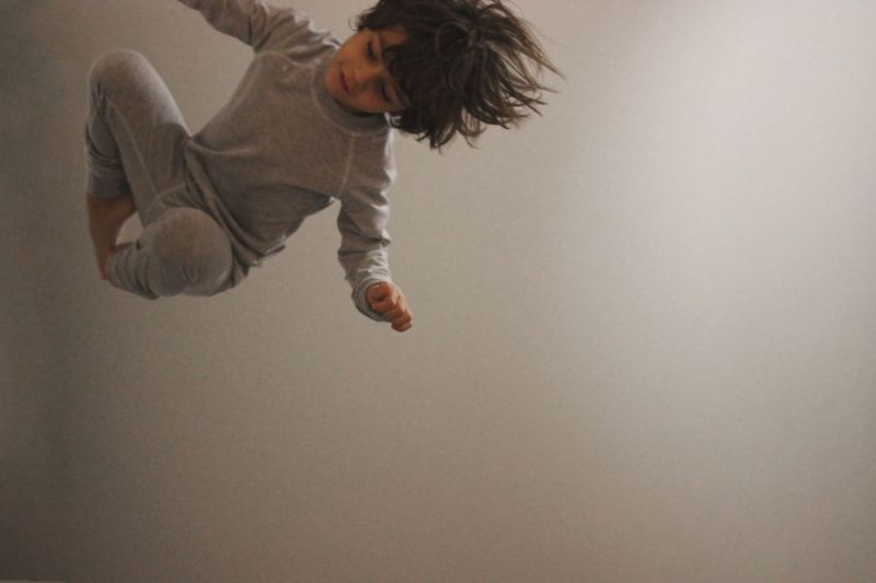 Full length of boy jumping by wall at home