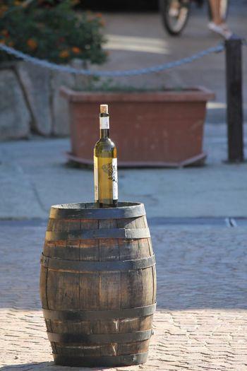 Wine bottle on barrel over footpath