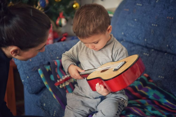 Cute Boy Playing Guitar With Mother At Home