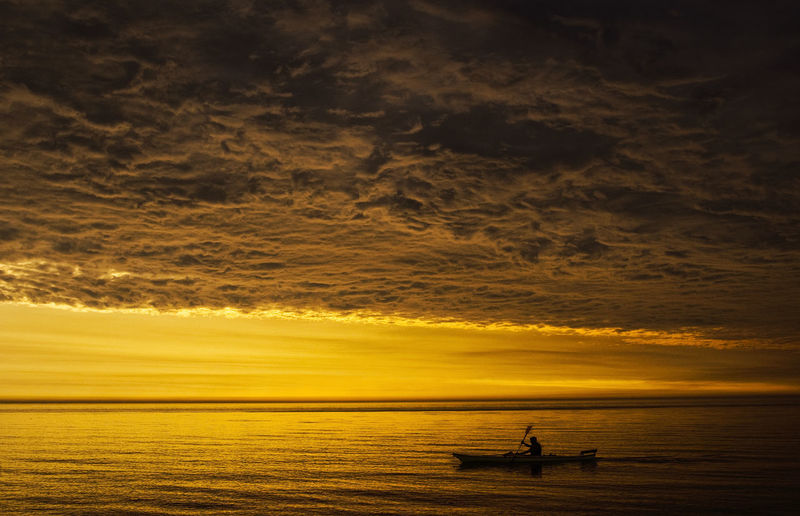 Silhouette Man Sailing In Boat On Sea Against Cloudy Sky During Sunset