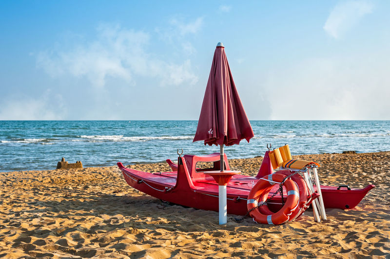 Lifeguard tools, umbrella, lifebuoy and rescue boat against beach, sea and sky Beach Beauty In Nature Boat Chair Coast Day Horizon Over Water Lifebuoy Lifeguard  Nature No People Outdoors Red Sand Scenics Sea Shore Sky Tranquility Water