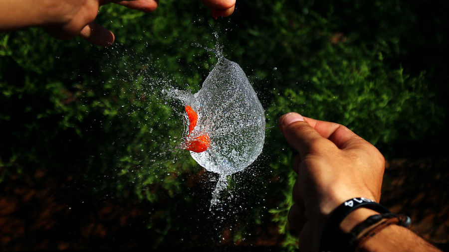 Cropped image of hands exploding water balloon