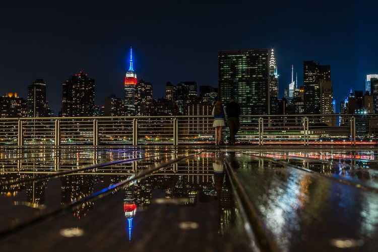 Rear View Of Man And Woman At Gantry Plaza State Park In City During Night
