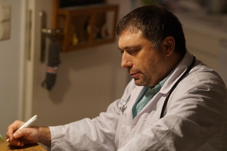 Side View Of Mature Doctor With Pen Sitting In Hospital