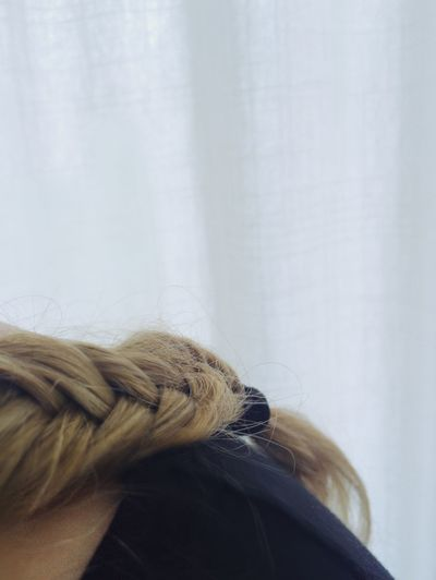 Cropped image of woman with braided hair at home