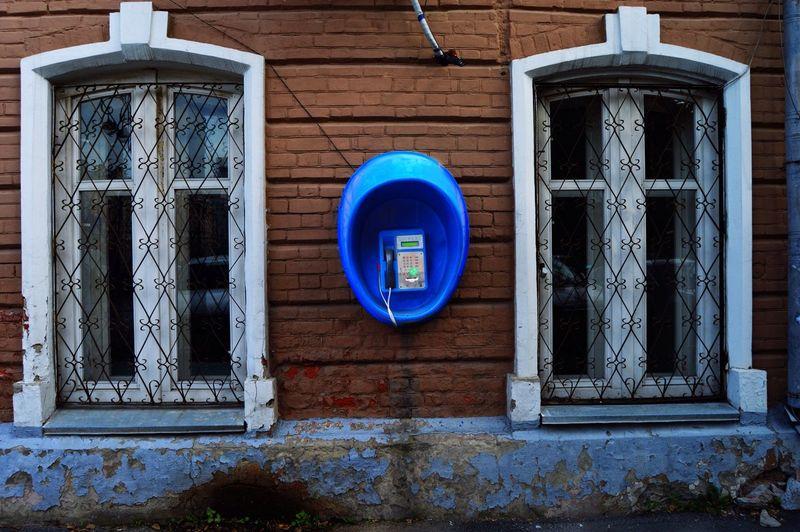 Blue pay phone on wall amidst windows