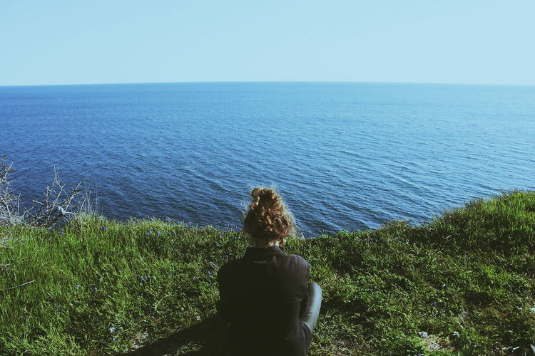 Woman Sitting On Grass Cliff Overlooking Calm Sea Against Clear Sky