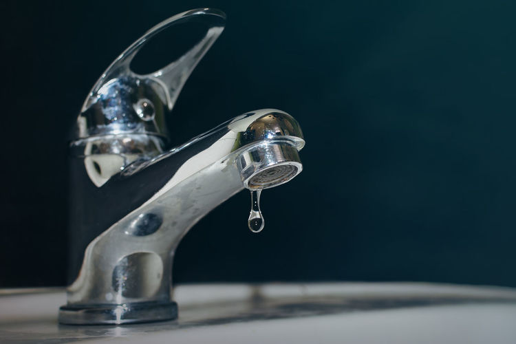 Close-up of water faucet against black background