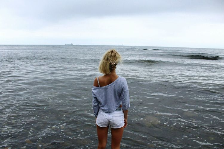 Rear View Of Young Woman Standing At Beach Against Sky