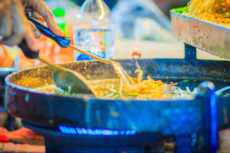 Close up hand of vendor during cooking for Padthai, the original Thai Fried Noodle, stir-fried noodle with shrimp and egg commonly served as a street food popular in Thailand Khao San Rd Khao San Road KhaoSan Khaosan Rd. Khaosandroad Pad Thai Shrimp Pad Thai With Shrimp PadThaiGoongSod Khao San Khao San Knok Wua Khao San Rd. Khaosan Road Khaosanroad Night Market Night Market In Thailand Pad Thai Pad Thai Kung Pad Thai Noodles Pad Thai Seafood Padthai Padthai Food Padthai Grassnoodle Padthainoodle Street Food Market