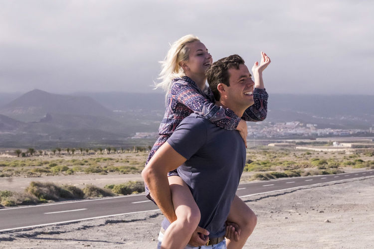 Side View Of Man Piggybacking Girlfriend On Road Against Sky