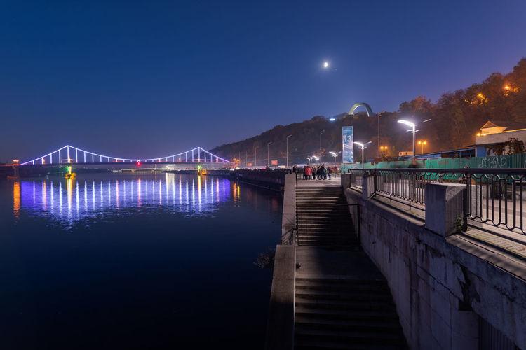 Illuminated bridge over river against sky at night