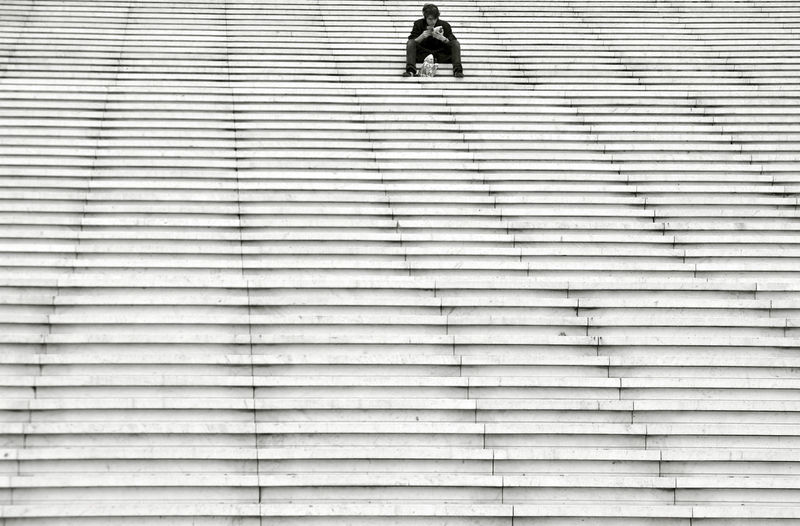 Low angle view of man sitting on staircase
