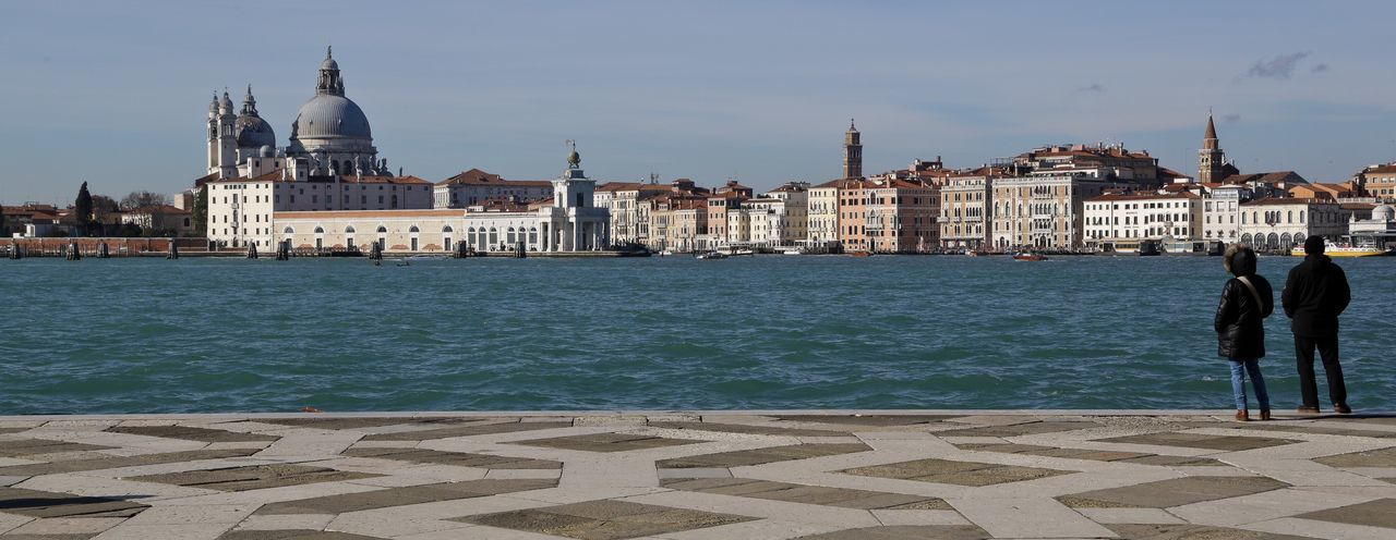 Panoramic view of santa maria della salute in front of canal on sunny day