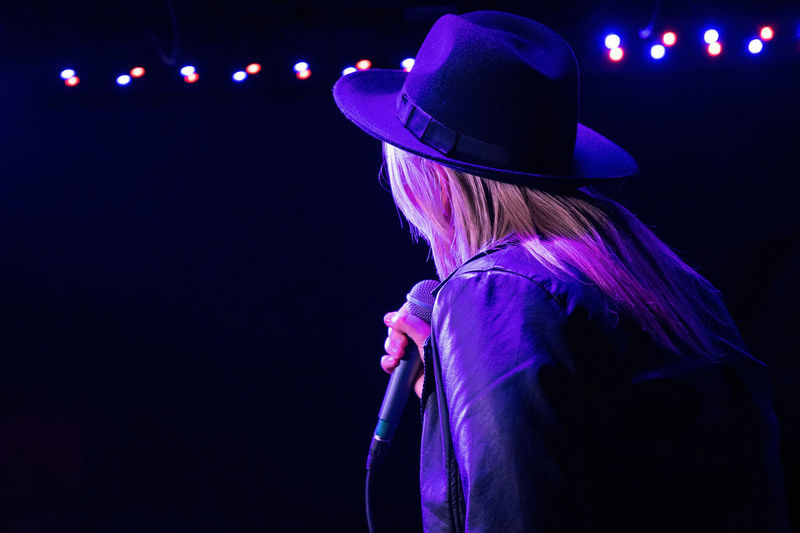 Rear view of woman wearing hat against black background