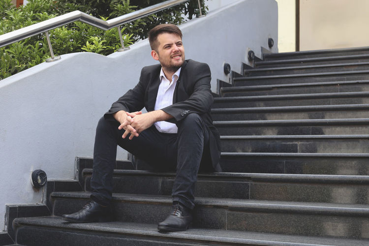Staircase Sitting Steps And Staircases One Person Well-dressed Business Person Young Adult Business Formalwear Contemplation Entrepreneur Successful Black Jacket Kick Start Smiling Businessman Millennials Young Men Front View
