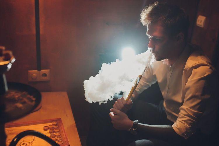 Young man smoking hookah at home