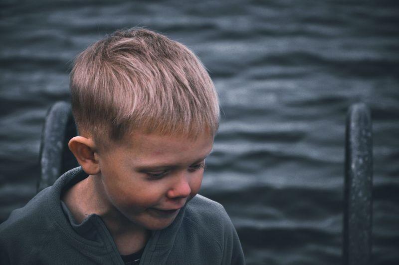 Portrait of boy looking at sea shore