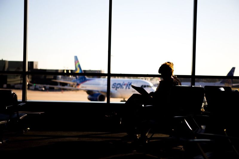 Silhouette man sitting at airport against sky