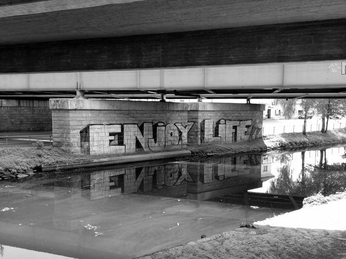 Water Text Bridge - Man Made Structure Day No People Outdoors Architecture Nature Reflection Sunlight Blackandwhite Photography Black&white Graffiti Text Eyeemphonephotography Phonephotography📱 Building Exterior Outdoors Photograpghy  Architecture Blacckandwhite