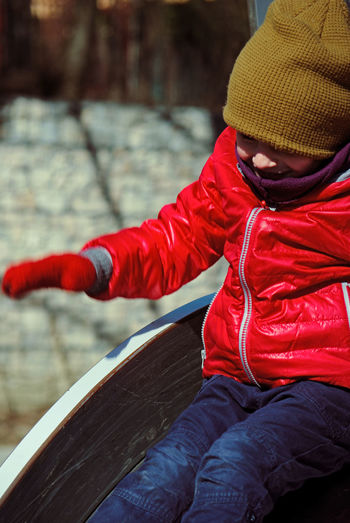 Cute boy wearing warm clothing while sitting on slide in playground