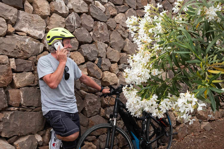 Relaxed moment for a senior caucasian man enjoying e bike bicycle in the nature. Resting and talking on mobile phone. White hair and beard. Yellow helmet. Stones and flowering plants on background 70 Years Active Activity Adult Aged Background Beard Beautiful Bicycle Bright Casual Caucasian E Bike Elderly Electric Enjoying Excursion Fast Flowering Funny Grandfather Happiness Happy Healthy Helmet Hobby Lifestyle Man Mobile Phone Natural Nature One Pers Outdoor Outdoors Palm Trees People Plants Playing Retired Senior Sky Smiling Speedy Sport Sportswear Sunglasses Sunlight Talking Technology White Hair