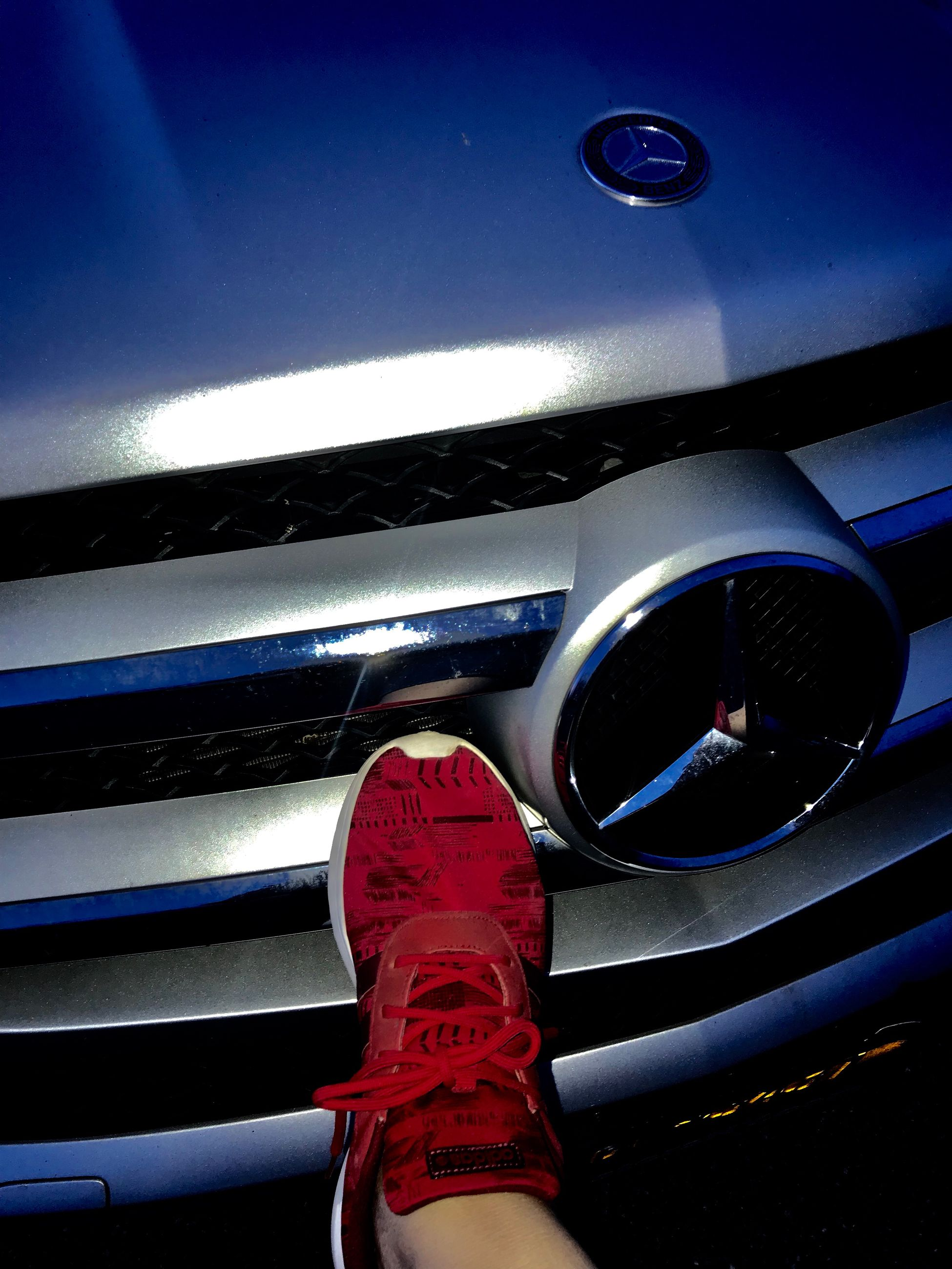 shoe, motor vehicle, car, land vehicle, transportation, mode of transportation, human body part, real people, personal perspective, low section, metal, blue, reflection, body part, one person, red, day, human leg, high angle view, close-up, human foot, chrome, human limb