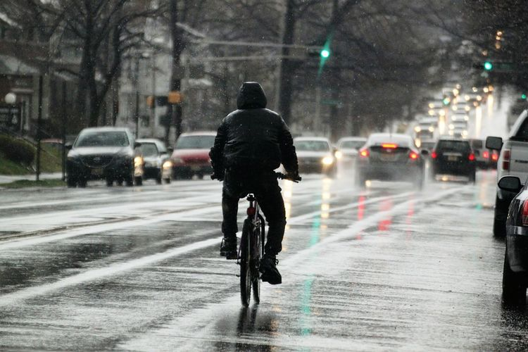 Rear View Of Man Riding Bicycle On Road In Winter