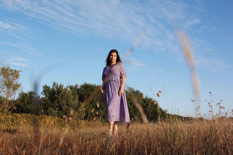 Portrait of woman standing on land against sky