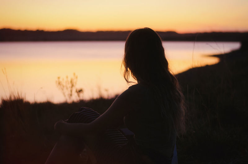 Silhouette woman sitting against orange sky during sunset
