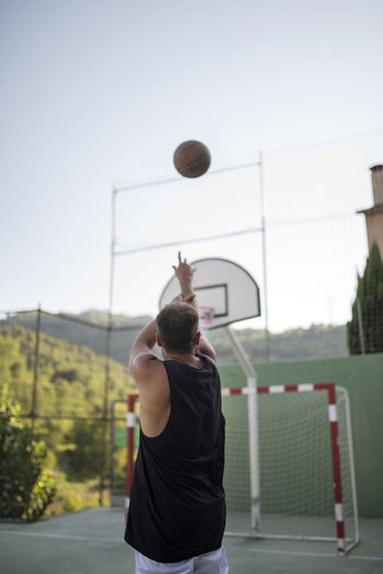 Rear view of man playing basketball against clear sky