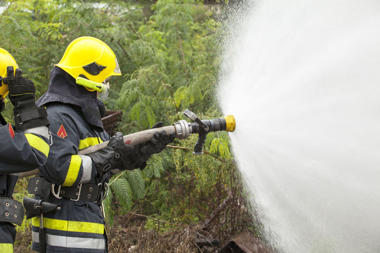 Firefighter in action Emergency Firefighter Spraying Spraying Water Action Danger Emergency Services Emergency Services Occupation Fire Fire Department Fire Department In Action Fire Department In Nature Fire Hose Firefighter Helmet Holding Outdoors Protective Workwear Pyromania Rescue Spraying Training Unrecognizable Person Water