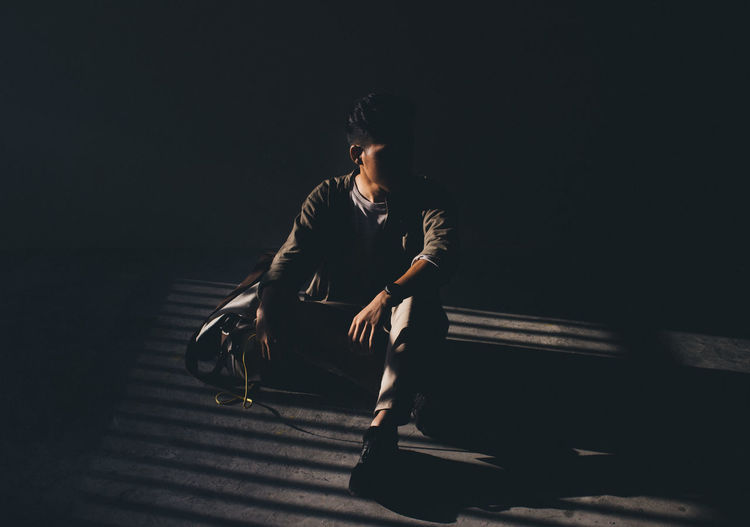 Young Man Sitting In The Dark