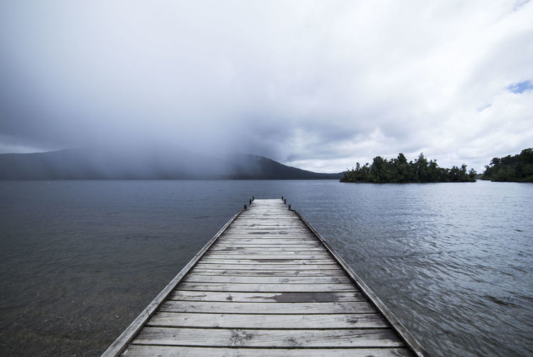 A jetty with storm clouds approaching. Bad Weather Darkness Plant Rain Storm Beauty In Nature Cloud - Sky Clouds Day Idyllic Jetty Lake Nature New Zealand No People Non-urban Scene Outdoors Pier Scenics - Nature Sky Tranquil Scene Water Wood - Material