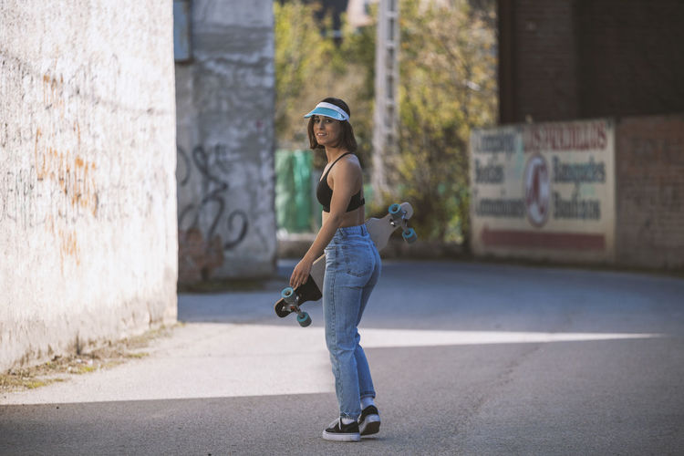 Girl with her skate on a town road near to old factory Girl Skateboarding Young Woman Tank Top Sexygirl Attractive Skatergirl Skater Village Sports Outdoors Outfit Casual Clothing 80s Style Leisure Activity Hobbies Jeans Jacket Brunette Short Hair Hairstyle Millennial Pink Youth Culture Viso Full Length One Person Lifestyles Sports Equipment Skateboard Focus On Foreground Road Young Adult Sport Street Outdoors Skill  Transportation Steet Sports