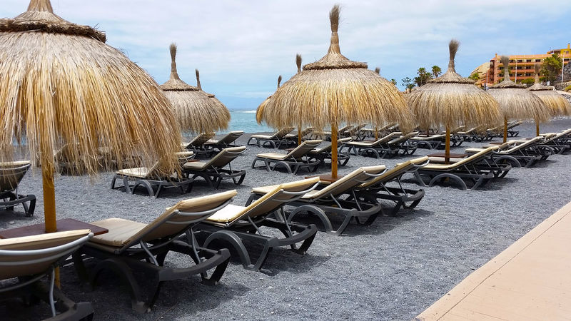 long row of straw umbrellas aligned and empty on the beach in front to the atlantic ocean in Tenerife island Absence Abundance Architecture Arrangement Blue Cart Chaise Longue City Cloud - Sky Day In A Row Large Group Of Objects Mode Of Transportation Nature No People Ocean Order Outdoors Sea Sky Straw Umbrellas Street Thatched Roof Travel Vacation