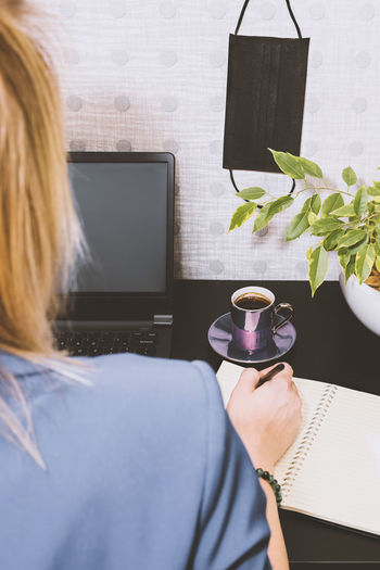 Rear view of woman holding coffee cup at home