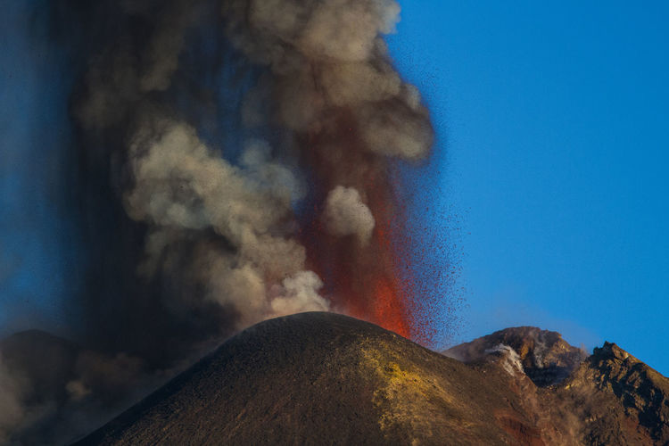 Volcanic eruption against blue sky