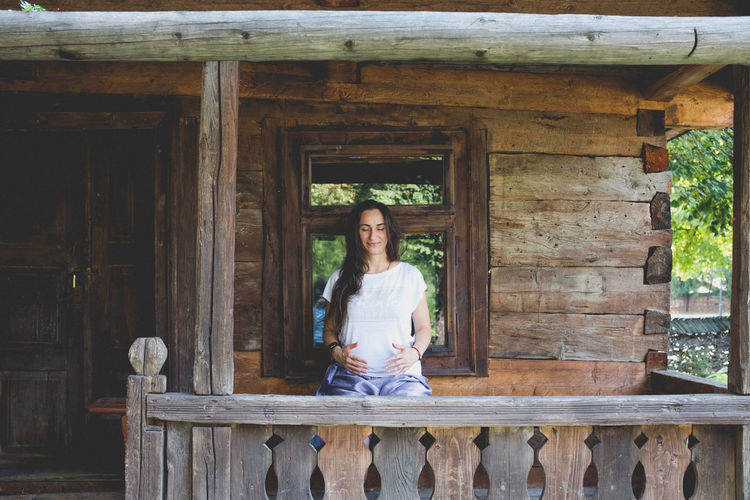 Young Woman Meditating Outside Wooden House